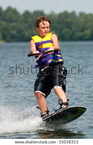 teen riding a wave on wake-board - stock photo