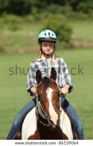 Teen riding her horse - stock photo