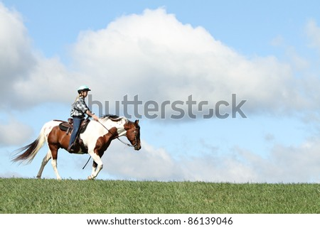 Teen riding horse - stock photo