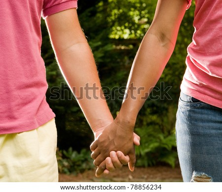 Teen romance - Hispanic boy and African American girl holding hands - stock photo