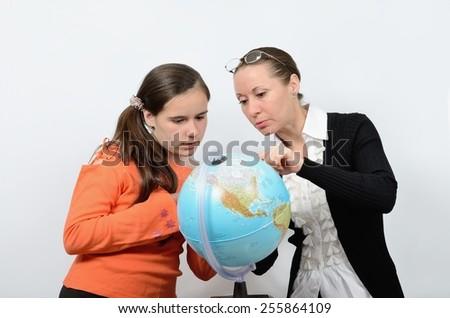 Teen schoolgirl and teacher woman engaged study globe - stock photo