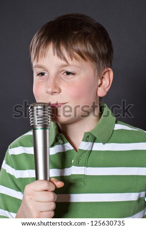 Teen singing into a microphone on a black background - stock photo
