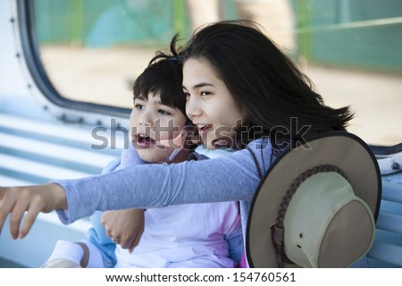 Teen sister taking care of disabled little brother, pointing off camera. Child has cerebral palsy. - stock photo