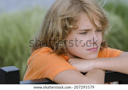 teen sitting on a bench worried about his actions - stock photo