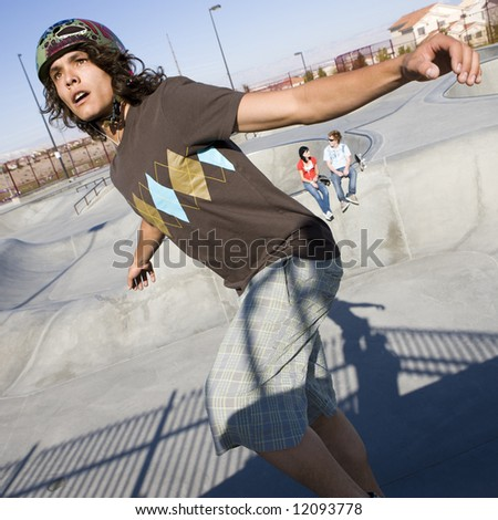 Teen skater does tricks at the skate park with his friends