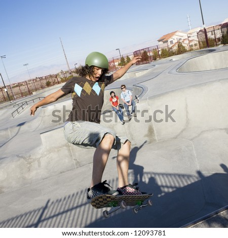Teen skater does tricks at the skate park with his friends - stock photo