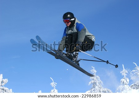 Teen ski jumping in fresh snow and sun - stock photo
