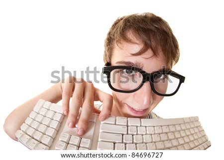Teen smiles behind a computer keyboard over white background - stock photo