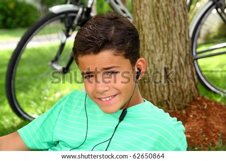 Teen smiling boy hearing music headphones grass sitting tree trunk - stock photo