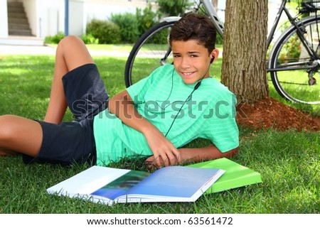 Teen smiling boy studying book garden headphones grass tree sitting - stock photo