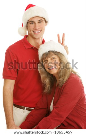 Teen son giving his mother rabbit ears during a family portrait.  Isolated on white.