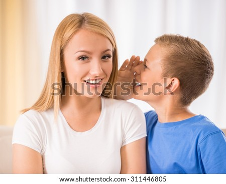 Teen son is whispering something to his mother. - stock photo
