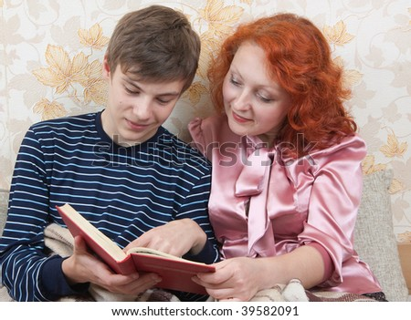 Teen son with mother read the book