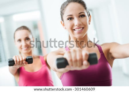 Teen sporty girls at gym exercising and weightlifting using dumbbells, body care and training concept - stock photo