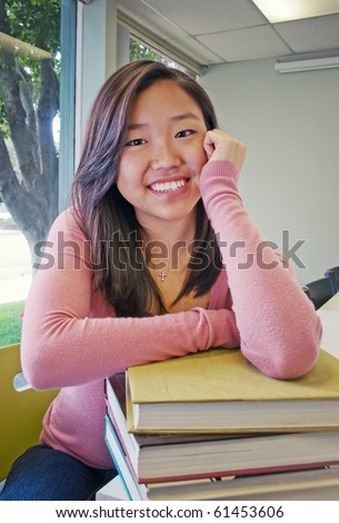Teen student girl with a stack of books to study - stock photo