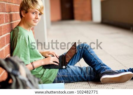 teen student using laptop in school passage - stock photo