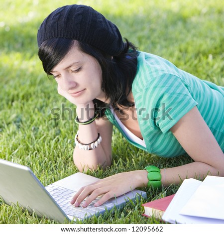 Teen studies with laptop in grass and smiles - stock photo