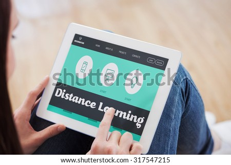 Teen using a tablet pc sitting on the floor against distance learning interface - stock photo