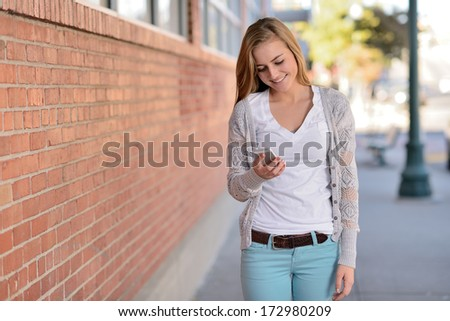 Teen using cell phone. Young woman looking at a smartphone while walking on a city street. - stock photo