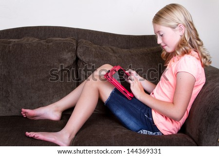 Teen using tablet while sitting or relaxing on couch