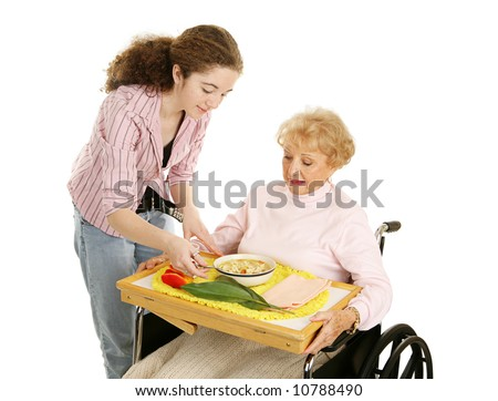 Teen volunteer brings lunch to a disabled senior woman.  Isolated on white. - stock photo