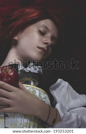 Teen with a red apple lying, tale scene - stock photo