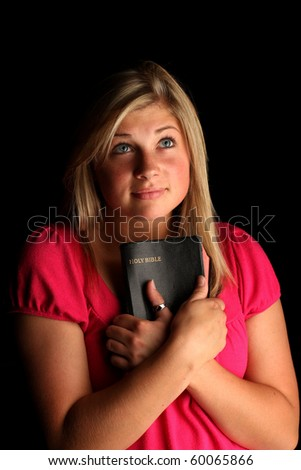 Teen with bible on black background, low key lighting technique - stock photo