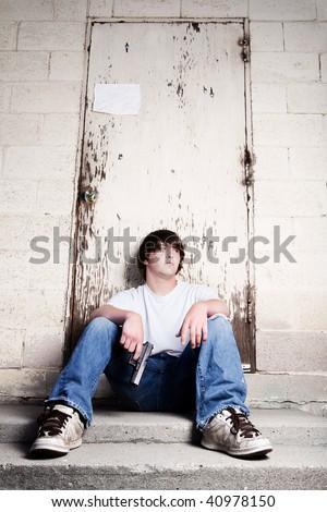 teen with handgun - teenager against wall holding gun - stock photo