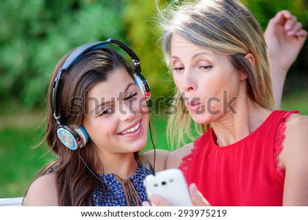 Teen with her mother listening music together with complicity - stock photo