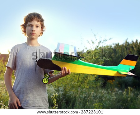 Teen with homemade radio-controlled model aircraft (airplane is hand made not copyright) - stock photo
