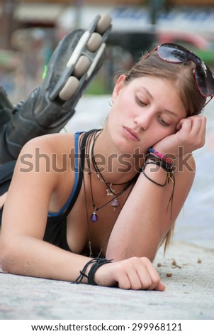 Teen with roller skate relax as she lying down in the park
