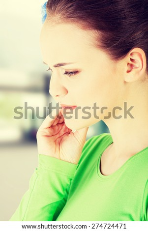 Teen woman pressing her bruised cheek with a painful expression - stock photo