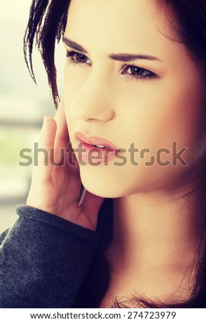 Teen woman pressing her cheek with painful expression - stock photo