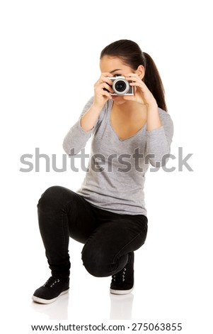 Teen woman taking a photo with a camera. - stock photo