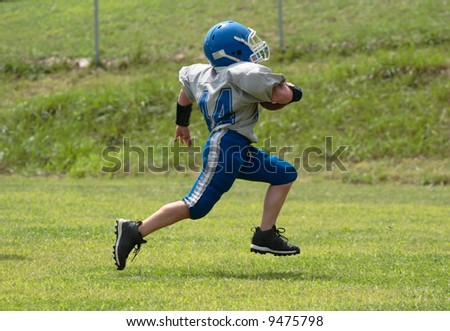 Teen Youth Football Player Running for the Touchdown - stock photo