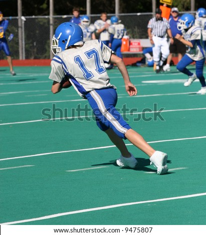 Teen Youth Football Player Running With the Ball - stock photo