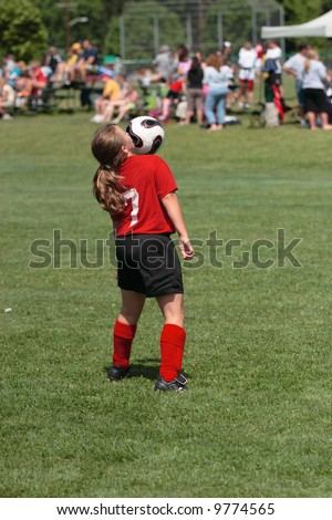 Teen Youth Girl Bouncing Soccer Ball off Chest during Game - stock photo