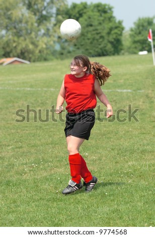 Teen Youth Girl Bouncing Soccer Ball off Head During Game. - stock photo