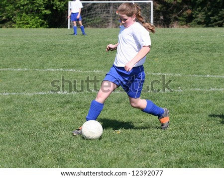 Teen Youth Girl Kicking Soccer Ball down the field - stock photo
