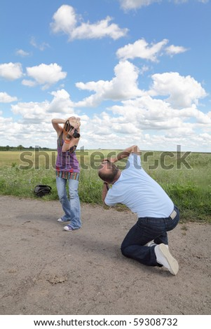 Teenage and middle age photographers photographing each other - stock photo