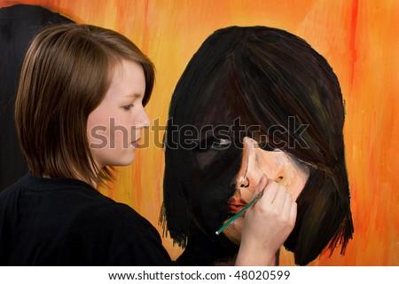 Teenage artist painting self-portrait - stock photo