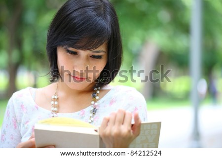 Teenage Asian girl reading a book in park - stock photo