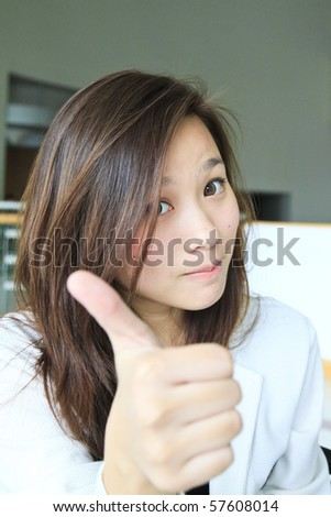 Teenage asian girl showing thumbs up with smiling on face - stock photo