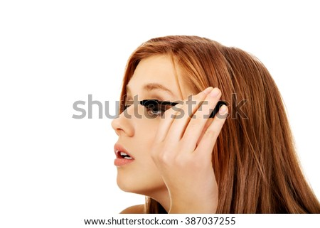 Teenage beautiful woman applying mascara - stock photo