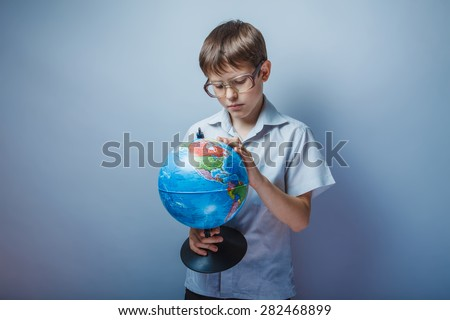 Teenage boy about ten years old European appearance in a light brown shirt and glasses consider globe on gray background, curiosity, knowledge - stock photo