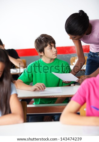 Teenage boy and African American teacher looking at each other at desk with classmates in classroom - stock photo