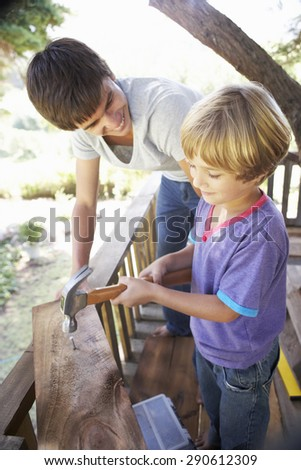 Teenage Boy And Brother Building Tree House Together - stock photo