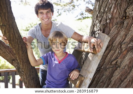 Teenage Boy And Brother Playing In Tree House Together - stock photo