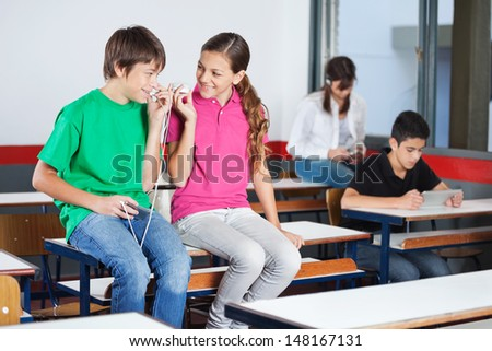 Teenage boy and girl looking at each other while listening music on mobilephone in classroom - stock photo