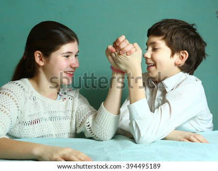 teenage boy and girl siblings play arm-wrestling close up laughing struggle portrait on blue wall background